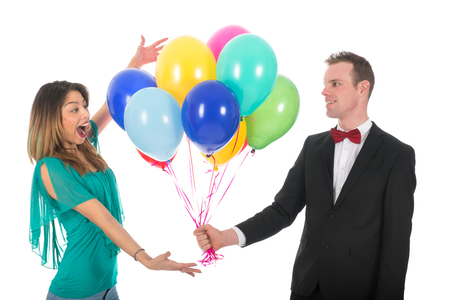 blowed: Young man with a bunch of colorful balloons making his girl friend happy solated over white background