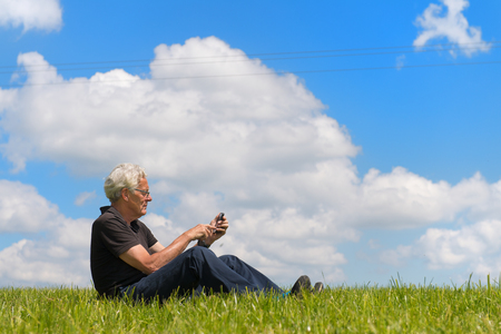 Senior man sitting in nature with mobile phone photo