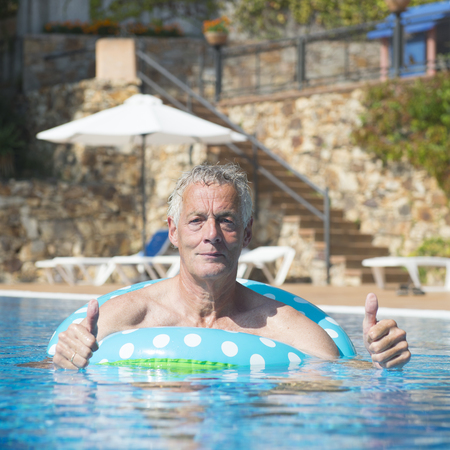 Vacation by senior man playing in swimming pool photo