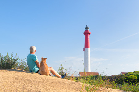Man and his dog sitting on dune and looking to Lighthouse red and white at the French west beach photo