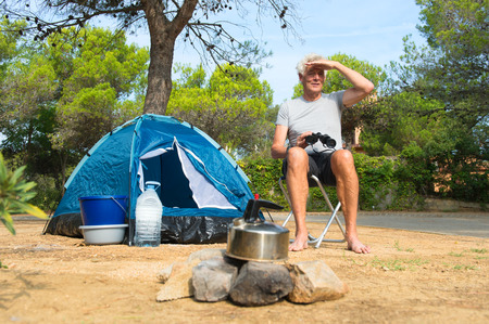 Man camping alone with blue dome tent and spyglass for adventure photo