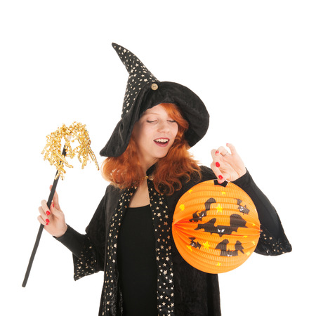 Young woman with red hair as evil witch during halloween isolated over white background Stock Photo
