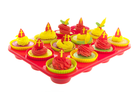 Dutch Sinterklaas cupcakes with mitre in red iand yellow solated over white background Stock Photo