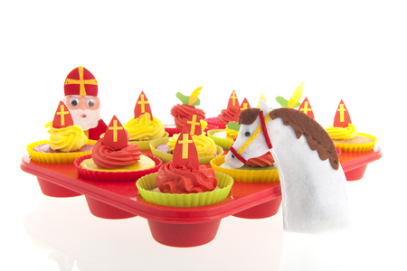 pete: Dutch Sinterklaas cupcakes with mitre in red iand yellow solated over white background Stock Photo