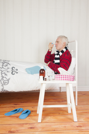 Senior sick man sitting in bed with medicines Stock Photo