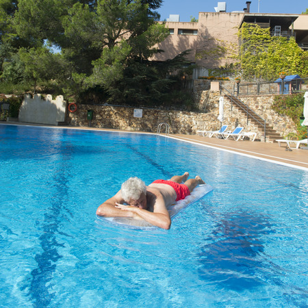 Senior man on vacation floating on water in swimming pool Stock Photo