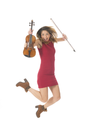 Young woman jumping high with violin music instrument isolated over white background Stock Photo