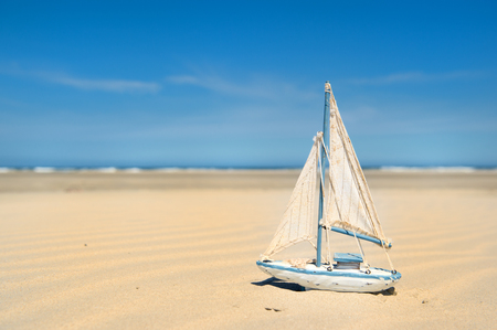 Miniature toy sail boat at the beach Stock Photo