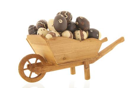 Wooden wheelbarrow full with chocolate easter eggs