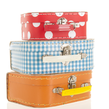Stacked colorful suitcases isolated over white background