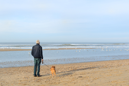 Man with dog in winter at the Northsea beach