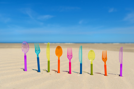 Colorful silverware standing in sand at the beach Stock Photo