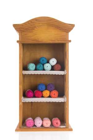 Open wooden cabinet with colorful knitting wool isolated over white background