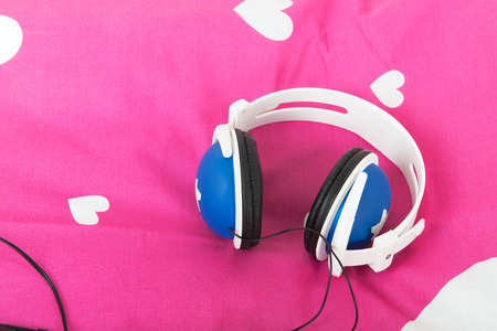 Head phones laying om pink bed