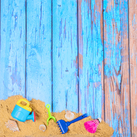 Beach poster on wooden background with sand and plastic toys Stock Photo