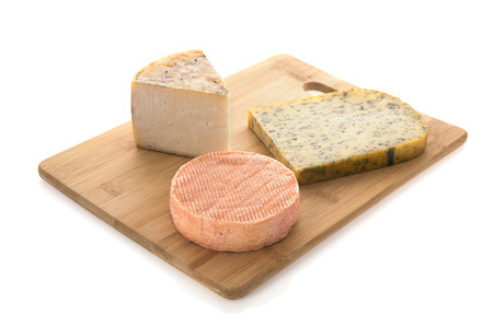 Assortment cheese on cutting board isolated over white background