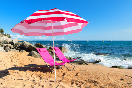Empty beach chairs with parasol with waves, sand and sea 免版税图像