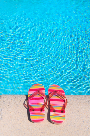 Colorful striped flip flops at the swimming pool