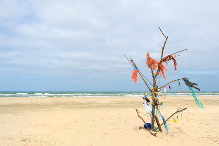 Landscape empty beach with tree made from rubbish at Dutch island Terschelling Фото со стока - 116984678