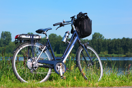 Blue e-bike or electical bike in front of river landscape