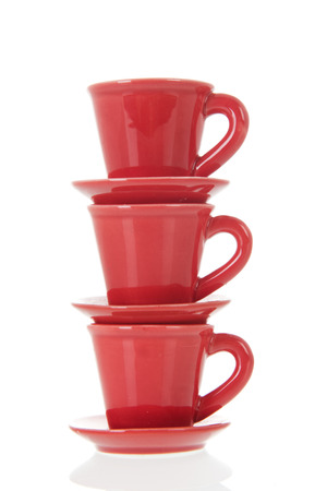 Stacked red cups and saucers isolated over white