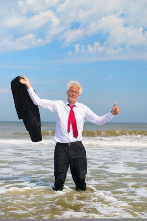 Business man in formal suit satisfied standing in the sea