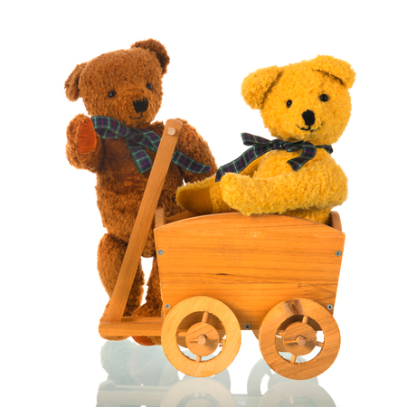 Stuffed bear toys with wooden cart isolated over white