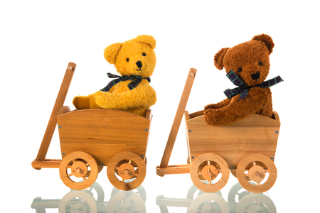 Stuffed bears toys in wooden carts isolated over white