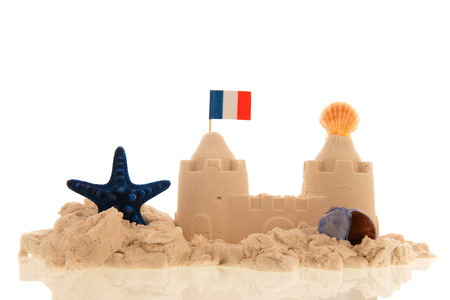 French sandcastle with red toys and flags isolated over white Reklamní fotografie