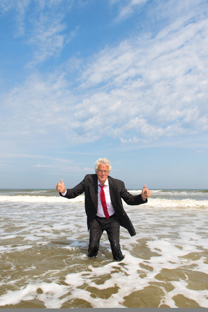 Business man in formal suit standing in the sea Stockfoto