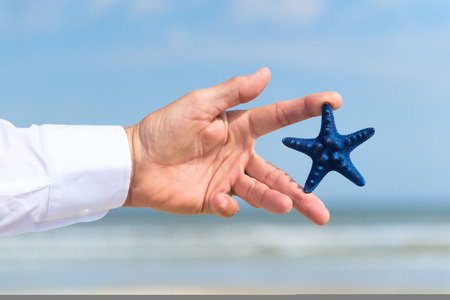 Blue starfish in hand of business man outdoor on vacation