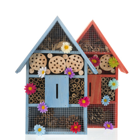 Two insect hotels with flowers isolated over white Stockfoto