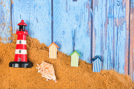 Lighthouse and beach huts in sand at the beach
