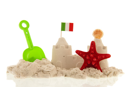 Italian sandcastle with red toys and flags isolated over white Standard-Bild