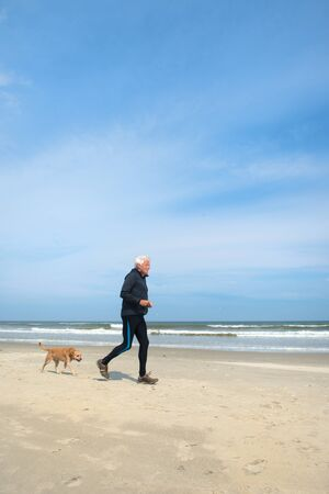 Healthy senior man as runner active with his dog at the beach