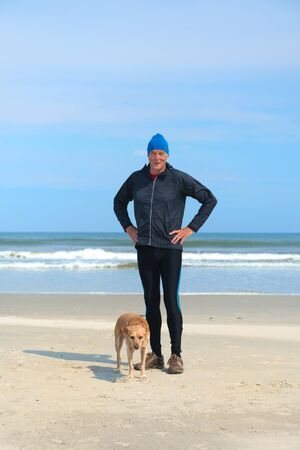 Healthy senior man as runner with his dog at the beach 版權商用圖片