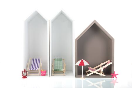 Modern beach houses with deck chairs isolated over white background
