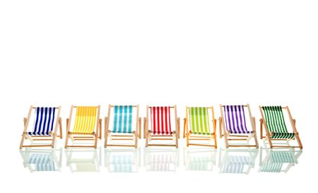 Row colorful beach deck chairs isolated over white background