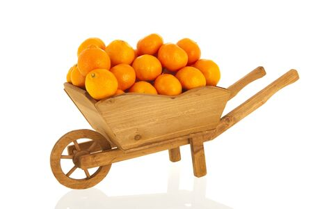 Wooden wheel barrow with mandarins isolated over white background