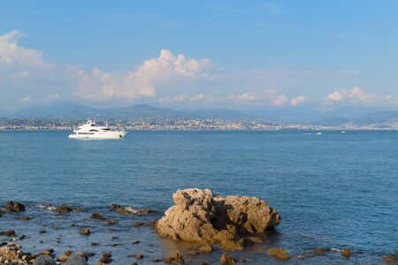 Yacht in the harbor of French Antibes with view on Nice