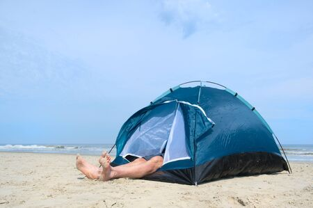 Single man sleeping in shelter at the beach