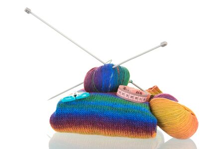 Colorful knitted jumper with needles and wool isolated over white background