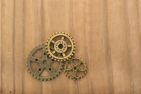 Industrial wheels in copper on wooden background