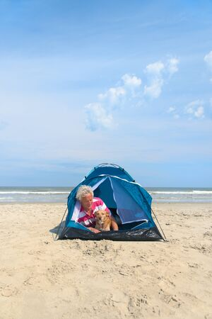 Single senior man with his dog camping in shelter at the beach Stock fotó