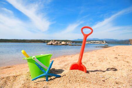 Korsischer Strand mit bunten Spielzeugen und Seesternen am Wasser