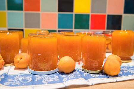 Making apricot jam in domestic kitchen