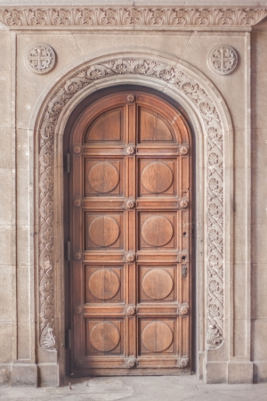 wooden arched door on a gothic stone building photo