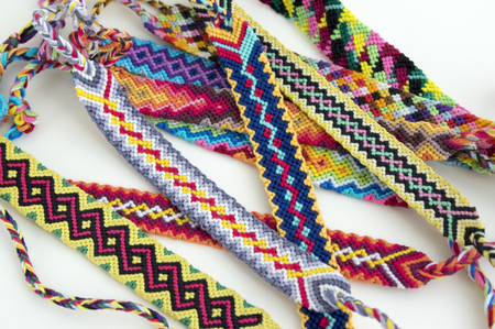 Handmade natural bracelets of friendship in a row, colorful woven friendship bracelets, background, rainbow colors Stock Photo