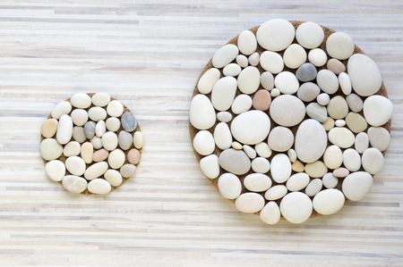 Two magic stone circles shape on white and gray stripped background, light pebbles, mandalas made of stones Stock Photo