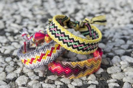 Three handmade homemade natural woven bracelets of friendship on stone background, friendship rainbow color bracelets, sunlight Stock Photo